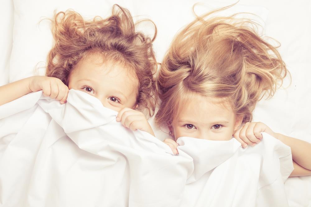 Uśmiechnięte dzieci leżą w łóżku