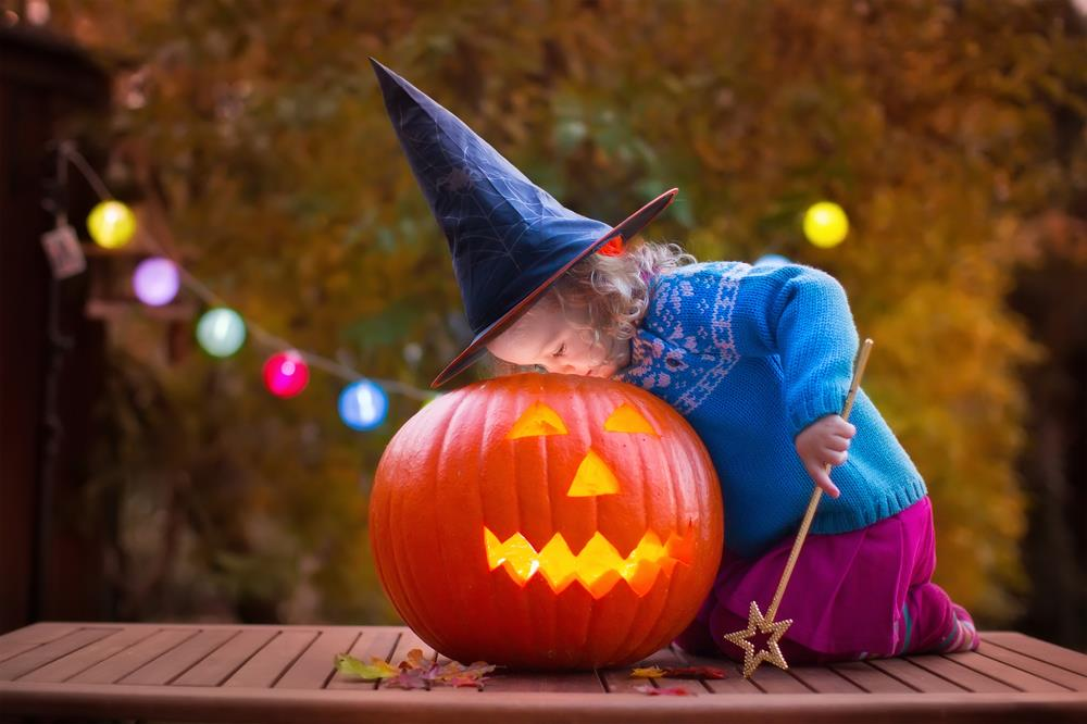 Dziewczynka zaglądająca do środka halloweenowej dyni