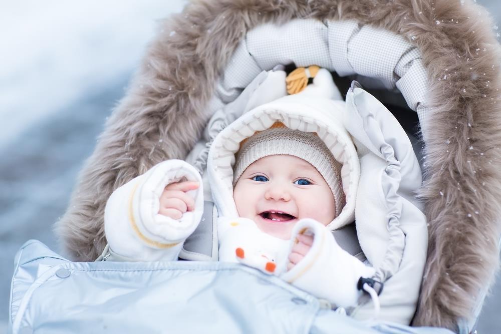 Dziecko w wozku ubrane w zimowy pajacyk