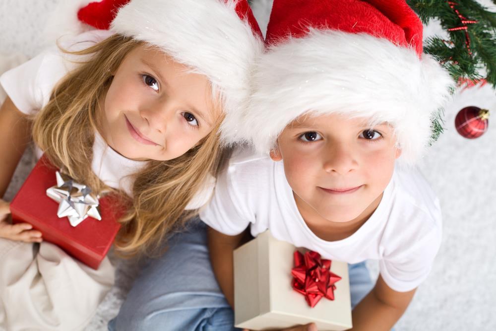 Dzieci w mikołajkowych czapkach trzymają prezenty