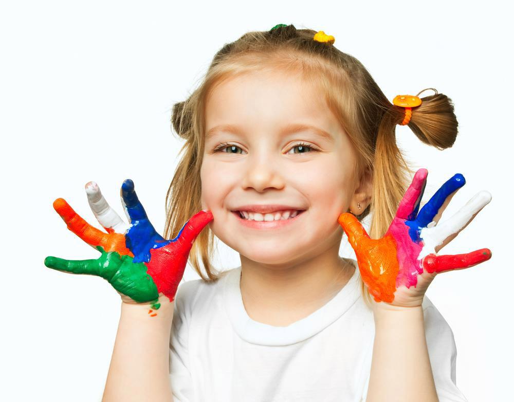 Uśmiechnięta dziewczynka z pomazanymi farbkami rączkami