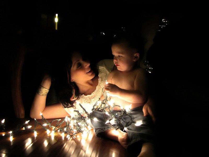 Mama i dziecko odpoczywają przy świątecznych światełkach