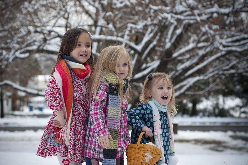 Trzy dziewczynki w zimowych płaszczach