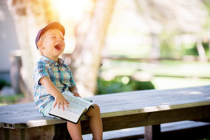Śmiejące się dziecko siedzące na ławce