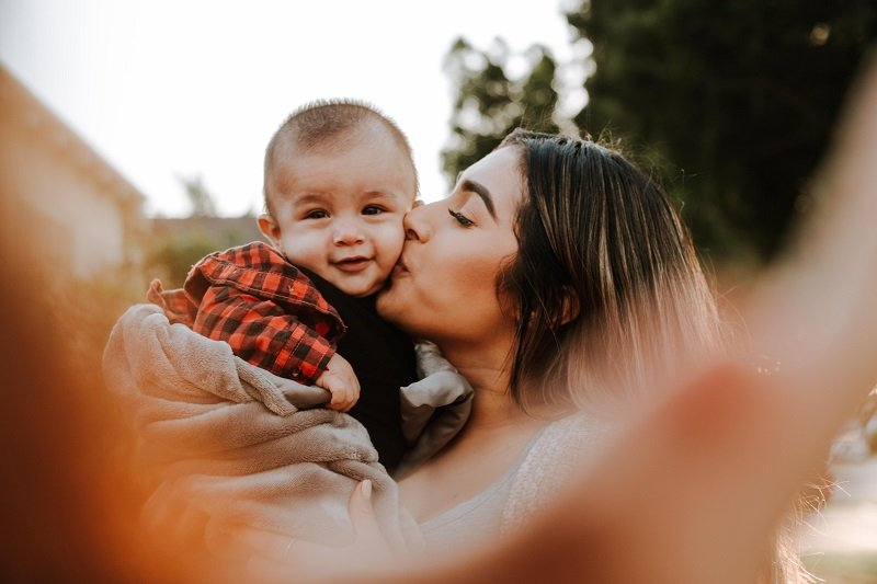 Matka całująca dziecko w policzek
